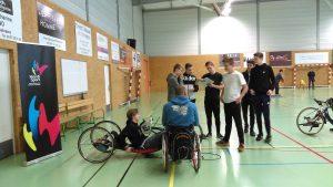 Eleves qui discutent avec un sportif en situation de handicap